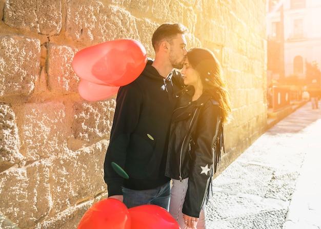 Individuo joven que abraza y que besa a la señora con los globos en la calle