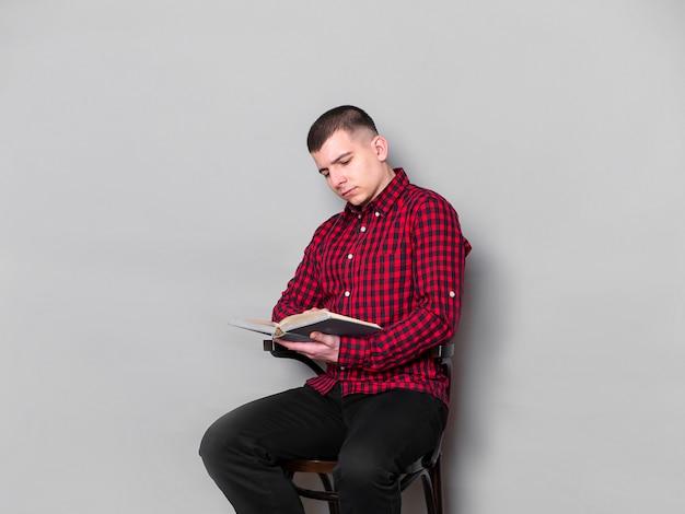 Individuo que se sienta en una silla y que lee un libro aislado en fondo gris.