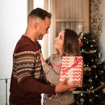 Individuo sonriente con la caja de regalo y la señora alegre cerca del árbol de navidad