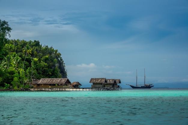 Indonesia. una isla tropical cubierta de selva. tarde nublada. yate y cabañas en el agua.