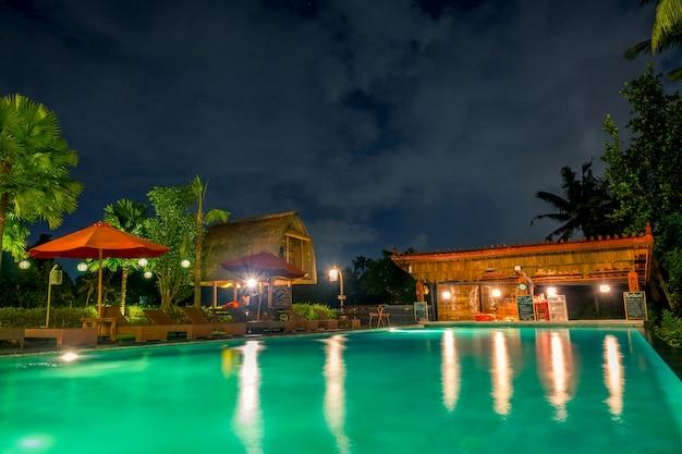 Indonesia. noche en la selva. piscina vacía y bar en el hotel.