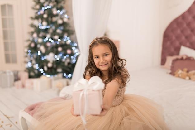 Infancia feliz, cuento mágico de navidad. pequeña princesa con el regalo de papá noel para navidad.