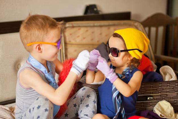 Infancia feliz. linda chica y chico jugando de una manera y con gafas de sol, gorras. adorables niños divirtiéndose en el interior.