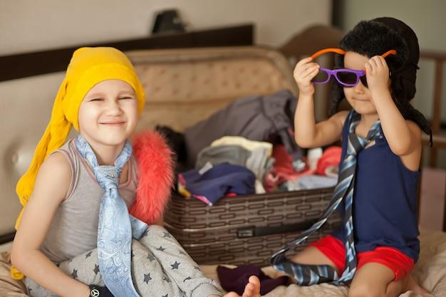 Infancia feliz. linda chica y chico jugando de moda y con gafas de sol, sombrero de vaquero. adorables niños divirtiéndose en el interior.