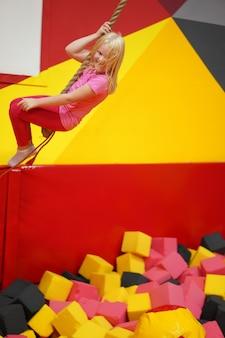 Infancia feliz de un niño moderno en la ciudad - niña en un parque de diversiones que monta una cuerda