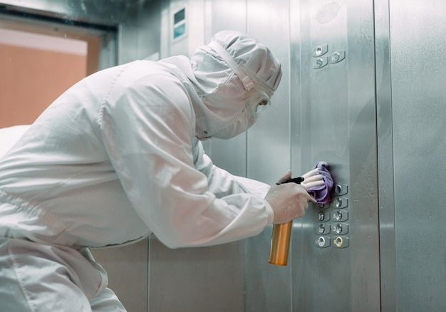 Infección de coronavirus. paramédico en máscara protectora y disfraz desinfectando un ascensor con rociador,