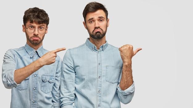 Infelices dos amigos jóvenes señalan a un lado como notar a su enemigo, tienen expresiones faciales hoscas