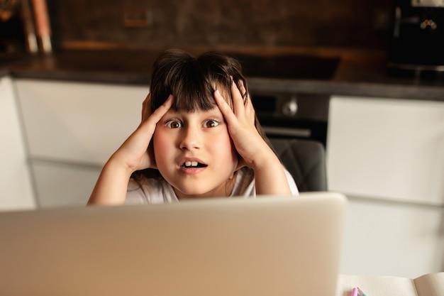 Infeliz colegiala. depresión y dolor de cabeza por el aprendizaje en línea en el hogar. niña sostiene su cabeza durante una lección en línea
