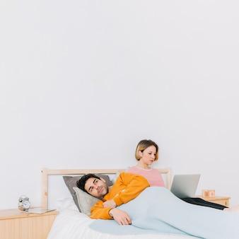 Infeliz hombre acostado cerca de la mujer con la computadora portátil