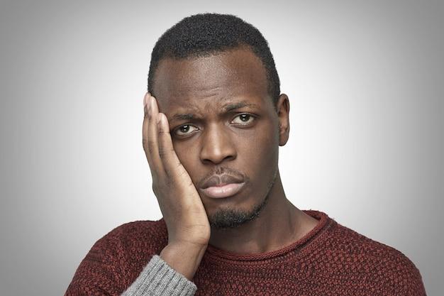 Infeliz hombre afroamericano que sufre de dolor de muelas y siente un gran dolor