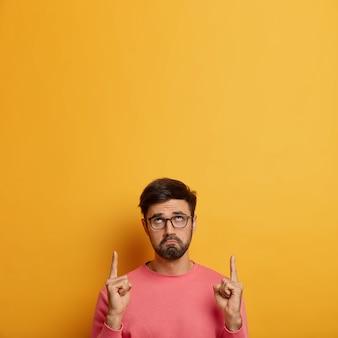 Infeliz hombre barbudo triste en gafas se ve con expresión sombría hacia arriba