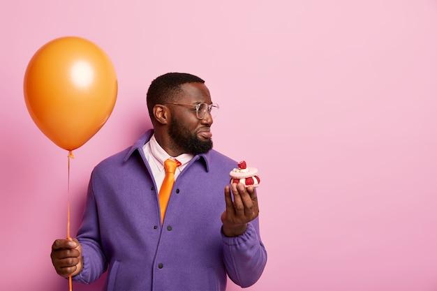 Infeliz hombre negro con barba cansado de la preparación de la fiesta, sostiene un globo de aire y una magdalena, mira con insatisfacción en el lado derecho, los invitados tristes no vinieron en el cumpleaños, viste una camisa blanca formal