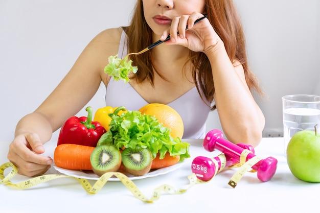 Infeliz joven asiática aburrida emoción en el momento de la dieta y se niega a comer verduras frescas en un tenedor en el comedor en casa, a la niña no le gusta el sabor de las verduras. concepto de comida sana. de cerca