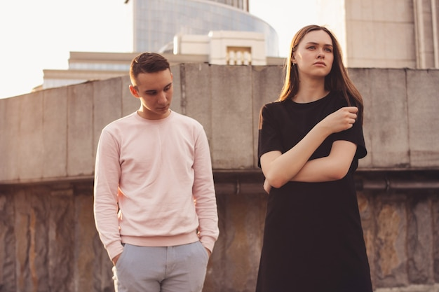 Infeliz joven pareja de amigos, adolescentes, estudiantes en la calle de la ciudad