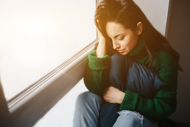 Infeliz joven está triste cerca de la ventana. la morena está llorando. tristeza, apatía, depresión y melancolía.