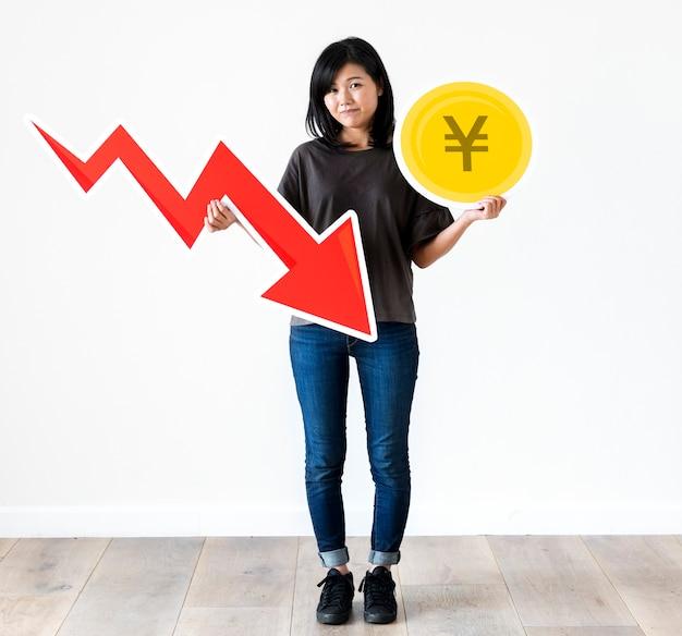 Infeliz mujer asiática sosteniendo un japón yenes y una flecha de disminución financiera