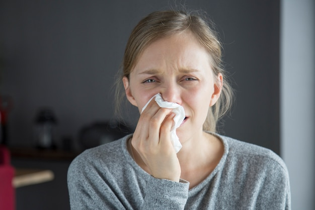 Infeliz mujer enferma que sopla la nariz con la servilleta, mirando a la cámara