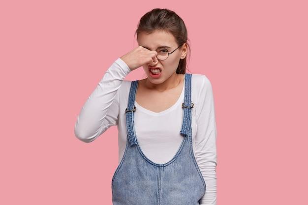 Infeliz mujer insatisfecha frunce el ceño, se tapa la nariz debido al mal olor, aprieta los dientes por el dolor