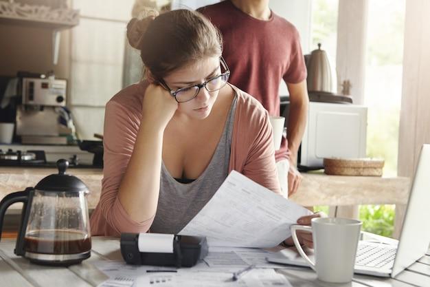 Infeliz mujer joven estresada vestida informalmente haciendo presupuesto doméstico, pagando facturas en línea usando una computadora portátil, sentada a la mesa con documentos y calculadora, sosteniendo papel y leyéndolo atentamente