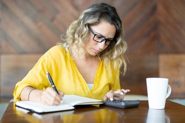 Infeliz mujer joven haciendo cálculos y tomando notas