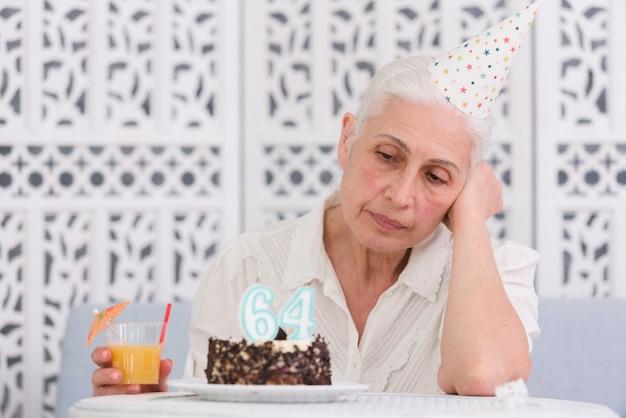 Infeliz mujer mayor mirando su pastel de cumpleaños con vaso de jugo en la mano