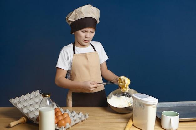 Infeliz niño caucásico en uniforme de chef de pie en la mesa de la cocina y frunciendo el ceño habiendo disgustado expresión molesta