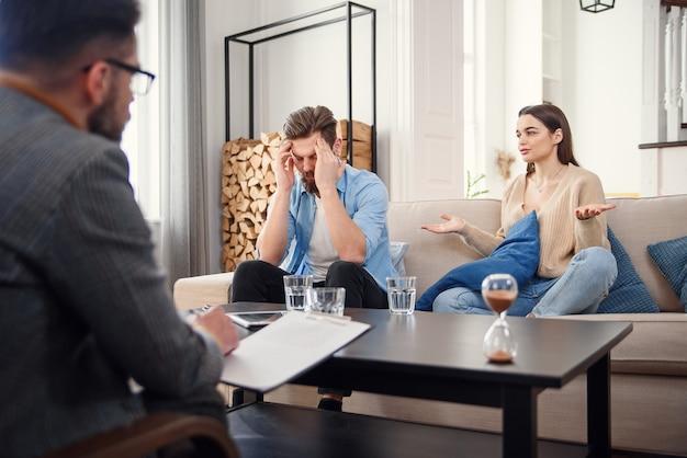 Infeliz pareja discutiendo, peleando, desacuerdo en la oficina de psicólogos, frustrada familia joven discutiendo problemas de relación con su terapeuta