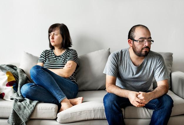 Infeliz pareja discutiendo en el sofá