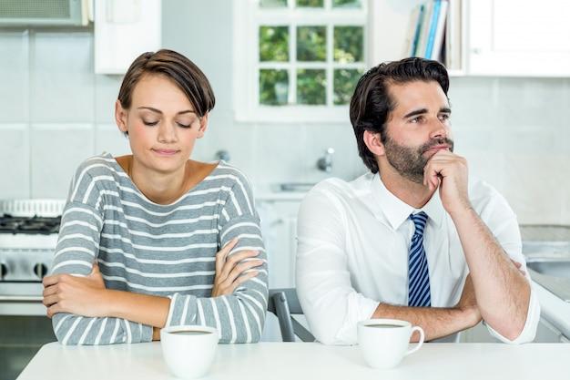Infeliz pareja sentada a la mesa en la cocina