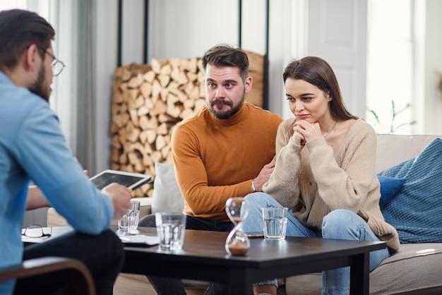 Infeliz pareja sentada en el sofá en la sesión de terapia en la oficina de terapeutas