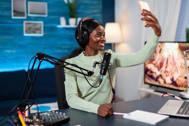 Influencer africano grabando podcast y tomando selfie en home studio. el anfitrión del programa de podcasts de internet de producción en línea en vivo transmite contenido en vivo, graba las redes sociales digitales.