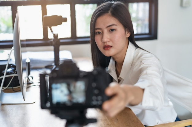 Influencer y creador de contenidos en conceptos de marketing digital. la mujer joven que ajusta su cámara digital se prepara para grabar el contenido del video a su canal.