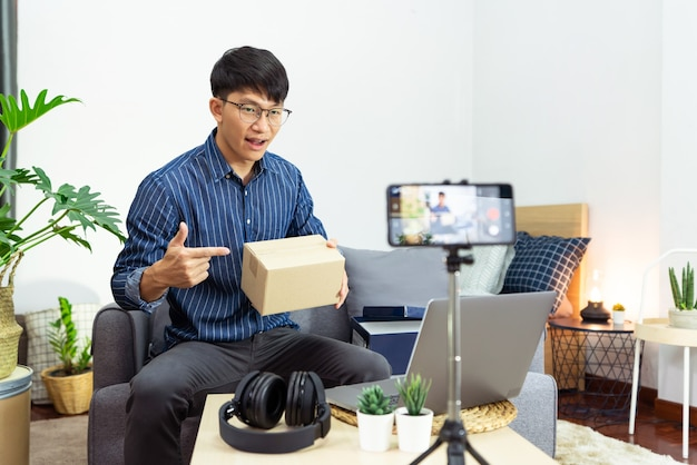 El influencer de las redes sociales o el blogger presentan y revisan la grabación o transmisión de vlogs sobre el producto utilizando un teléfono inteligente en un trípode para el canal de redes sociales que hace el concepto de transmisión en vivo.