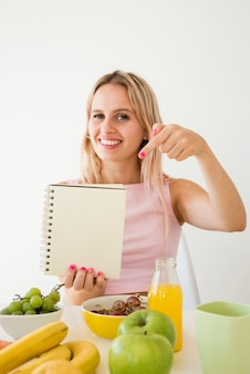 Influencer rubia enseñando cuaderno