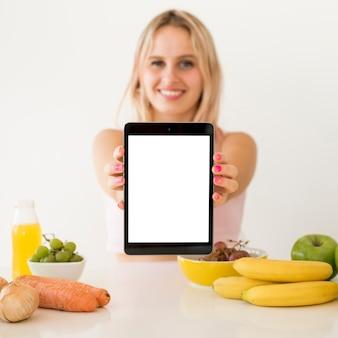 Influencer rubia enseñando tablet vacía