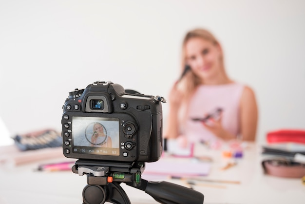 Influencer rubia grabando vídeo de maquillaje