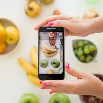 Influencer rubia haciéndole foto a fruta