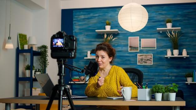 Influencer sentado en la estación de vlogs de casa mientras la cámara graba un nuevo podcast. programa en línea producción al aire transmisión por internet host que transmite contenido en vivo, graba comunicación digital en redes sociales