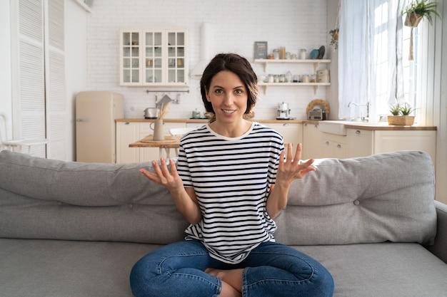 Influencer de vlogger de mujer sonriente grabando contenido nuevo en vlog, mirando la cámara web, sentado en el sofá.