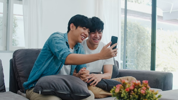 Influencia asiática pareja gay vlog en casa. los hombres lgbtq asiáticos felices se divierten y se divierten usando la tecnología del teléfono móvil, graban videos de estilo de vida y suben videos a las redes sociales mientras descansan en el sofá de la sala de estar.