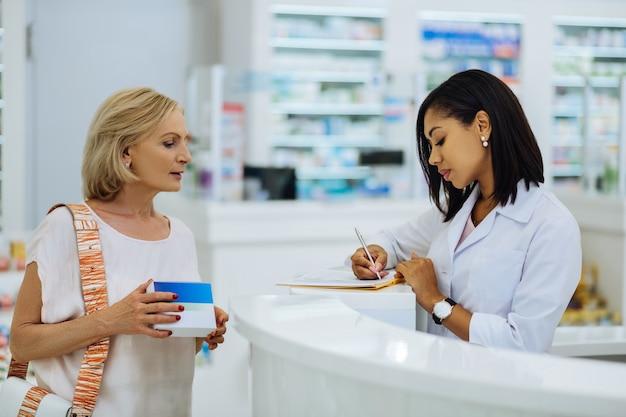 Información adicional. mujer rubia alegre hablando con el farmacéutico y sosteniendo el paquete con la medicina