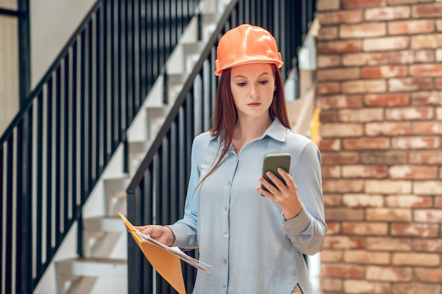 Información importante. grave joven en casco protector con plan de construcción mirando atentamente al teléfono inteligente cerca de las escaleras en el interior