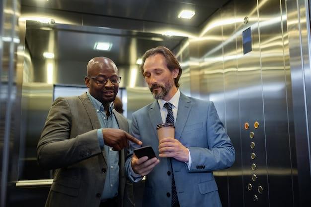 Información en el teléfono inteligente. dos hombres de negocios que leen información en el teléfono inteligente mientras usan el ascensor en el centro de negocios