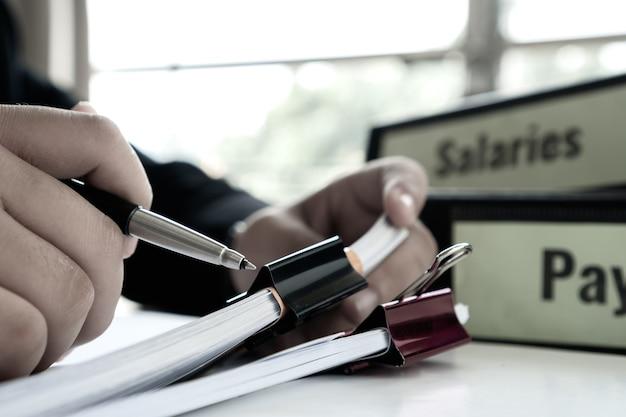 Informe de documento o concepto de gestión empresarial: manos del gerente de negocios sosteniendo el bolígrafo para leer, firmando documentos cerca de la carpeta de sueldos de nómina, informe resumido de recursos humanos y contabilidad empresarial de recursos humanos