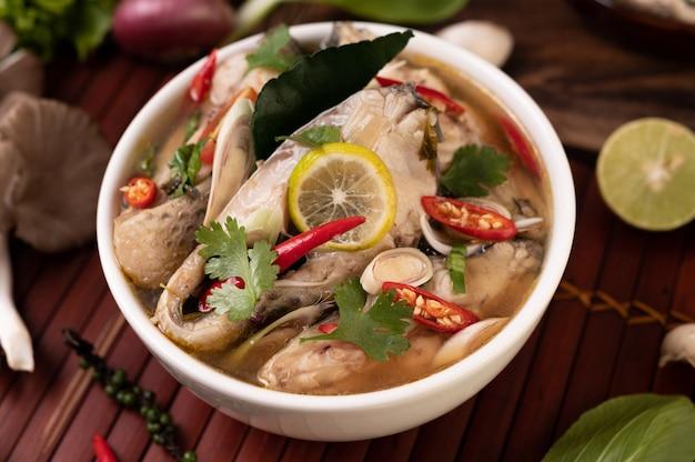 Infusión de pescado hervido con tomate, champiñones, cilantro, cebolleta y limoncillo en un bol