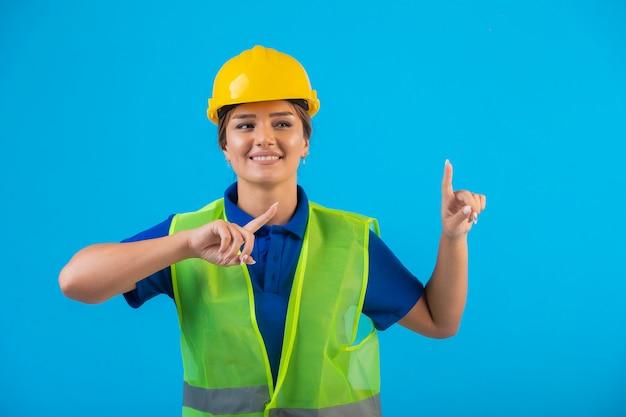 Ingeniera en casco amarillo y engranaje apuntando hacia arriba.