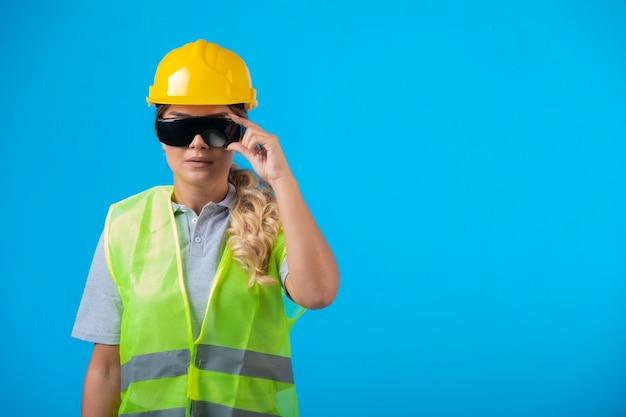 Ingeniera en casco amarillo y equipo con anteojos preventivos de rayos haciéndose pasar por un profesional.