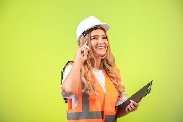 Ingeniera en casco blanco y equipo sosteniendo la lista de verificación y pensando.