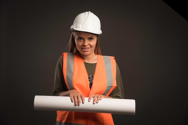 Ingeniera con un casco blanco que ofrece el plan del proyecto y se ve profesional.