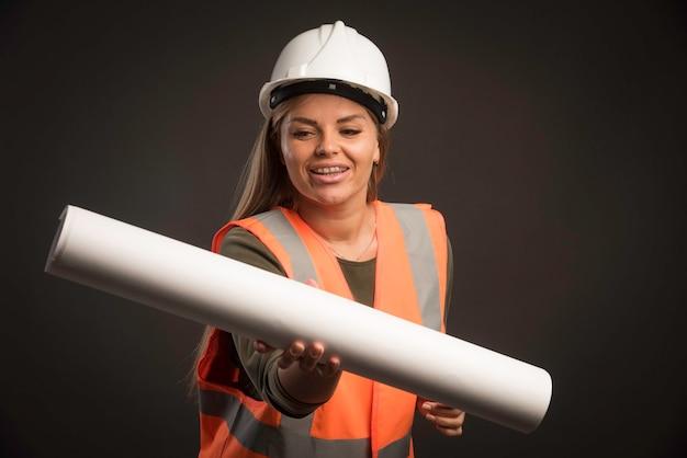 Ingeniera con un casco blanco sosteniendo el plan del proyecto y parece segura.